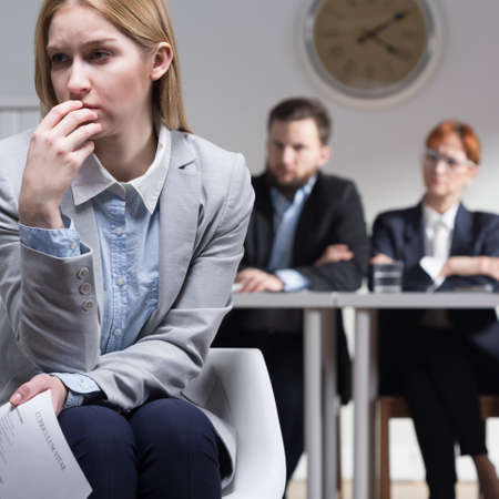 beside table: Sad woman holding CV and three businesspeople sitting beside table