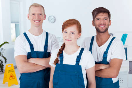 Team of smiling cleaners in an office Stock Photo