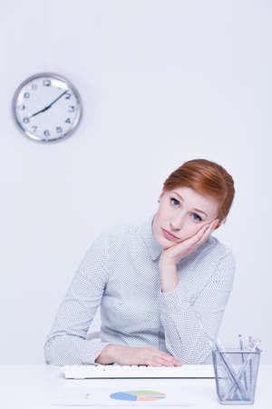 inefficient: Burnout woman at work sitting beside desk