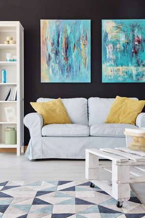 wall decor: Modern living room decor with paintings on the black wall
