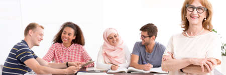 emigrant: Happy students in the classroom are sitting at the table and satisfied teacher smiling Stock Photo