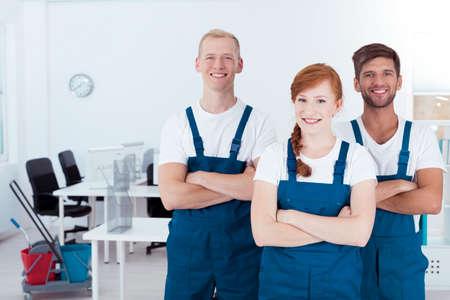 Grupo de jóvenes sonrientes limpiadores de pie en una oficina
