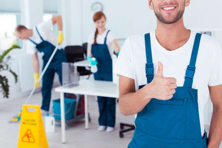 Glimlachende arbeider die zijn duim omhoog en zijn vrienden die werken in de achtergrond