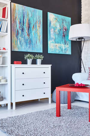 furnished: Red table, white chest of drawers and blue paintings in a modern room Stock Photo