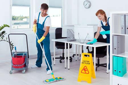 Groep jonge reinigingsmachines die in hun uniformen en het glimlachen werken