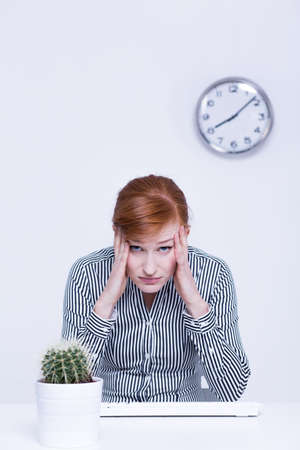 overworked: Sad and overworked woman sitting at light office