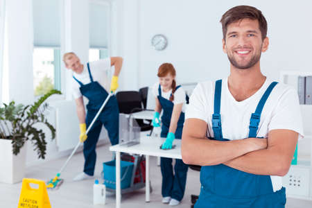Professional cleaner and his friends working in an office Stock Photo