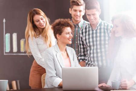 tormenta de ideas: equipo joven que tiene la lluvia de ideas, mujer de negocios usando la computadora portátil