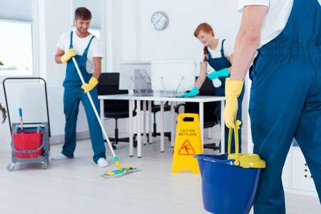 Bezette professionele schoonmakers die in een kantoor werken Stockfoto