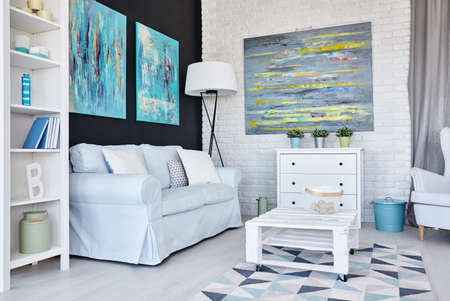 furnished: Creative white living room decorated with blue paintings