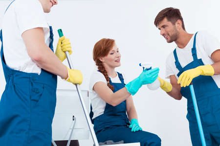 Three young professional cleaners working and talking Stock Photo
