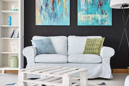 living room sofa: Cozy living room with sofa, cupboard, paintings and lamp