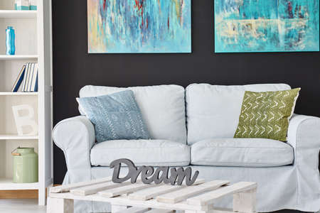 wall paintings: Grey sofa in modern living room with paintings on the wall Stock Photo