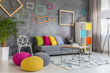 Spacious modern lounge with grey sofa and colorful pillows and poufs
