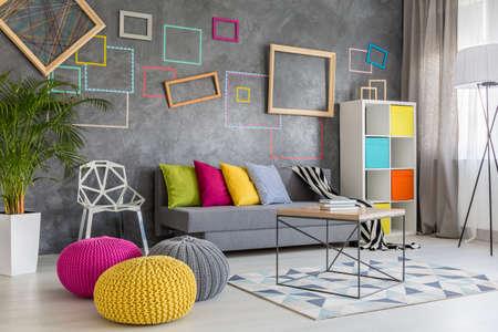 Ruime, moderne lounge met grijze bank en kleurrijke kussens en poufs