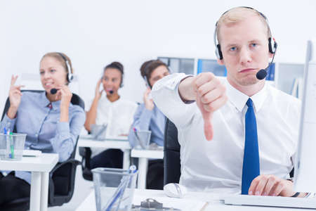 unsatisfied: Unsatisfied male telemarketer after talking with client Stock Photo