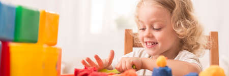 modeling clay: Panoramic close-up of a cheerful little girl playing with colourful modeling clay