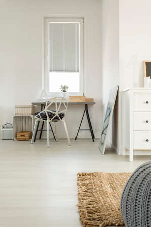 Study space with wooden desk in the corner of spacious bedroom Stock Photo