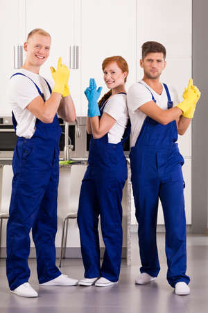 rubber gloves: Team of content professional cleaners wearing uniforms and rubber gloves