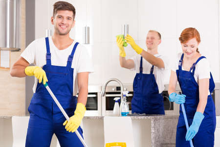 Cleaning team: Handsome cleaner with friends cleaning modern kitchen