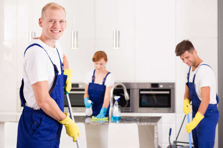 Cleaning team: House cleaner with friends tidying up kitchen