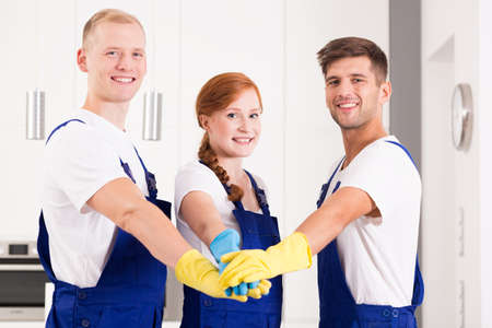 rubber gloves: Young domestic workers wearing uniforms and rubber gloves
