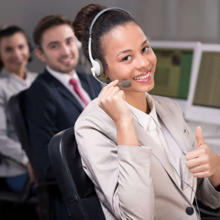 professionalist: Young female consultant is smiling and performing a thumb up gesture Stock Photo