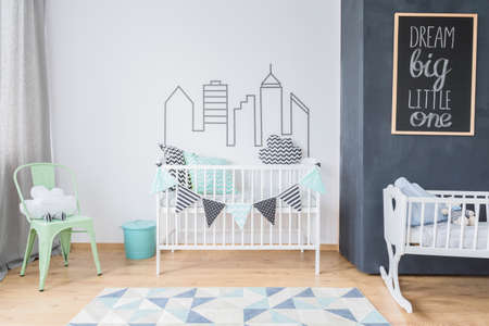wall decor: Newborns room corner with a white cot decorated with patterned garland