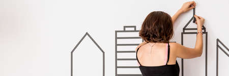 wall decor: Woman installing decorative wall sticker with cityscape