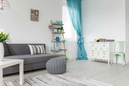 Living room in shades of gray and pastel colors with sofa bed, a dresser and a window Stok Fotoğraf