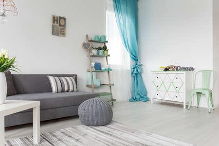 Woonkamer in tinten grijs en pastelkleuren met slaapbank, een dressoir en een raam