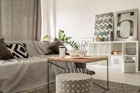 Tavolino in legno in salotto moderno bianco e grigio con divano