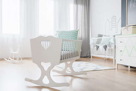 baby blue: Close-up of a decorative white cradle in a very bright baby room