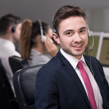 professionalist: Young male consultant smilling while his co-workers making conversations with clients Stock Photo