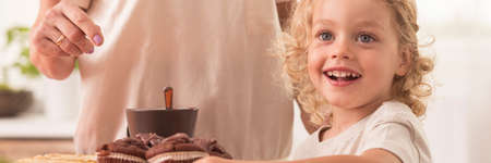 Happy little child in front of chocolate muffins, with grandma in the background Stock Photo