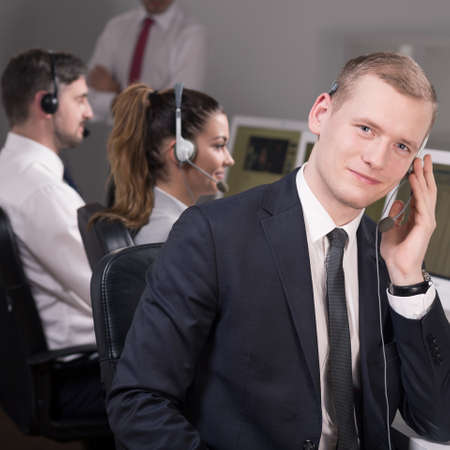 professionalist: Young male consultant is talking on the phone and his collegues are supervised by manager