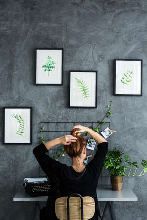 Woman working at the desk in plants apartment