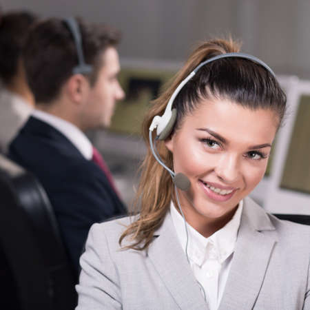 professionalist: Female smiling employee of call center with headset