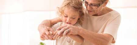 Lovely close-up of a little boy with grandma, baking with hands dirty in flour Stock Photo