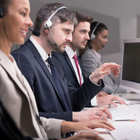 professionalist: Employees of call center are engrossed in work at the desk