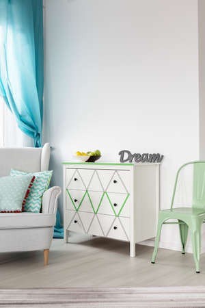 lightsome: View of part of bright living room with white chest of drawers, armchair and mint chair