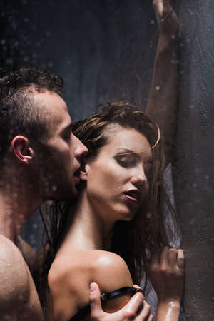 Naked man passionately kissing a woman in her ear while showering Foto de archivo