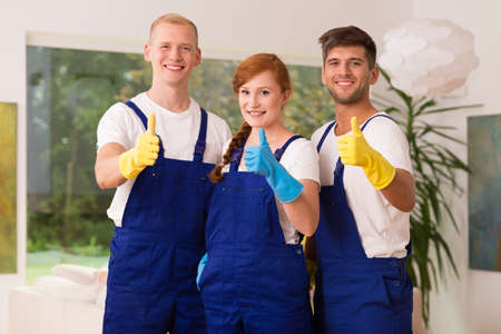 Young team of house cleaners showing thumbs up