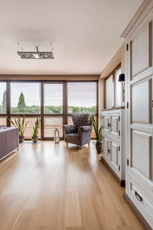 comfort room: Spacious room with stylish armchair, white cabinets, big windows and wooden flooring