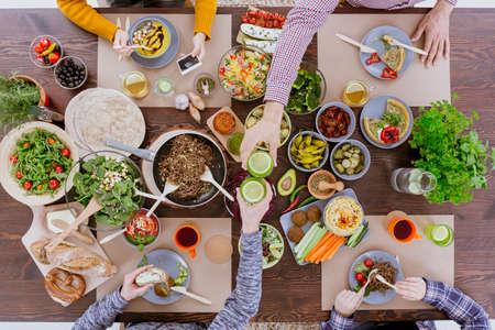 Mensen juichen tijdens gezond diner, zitten aan de rustieke tafel
