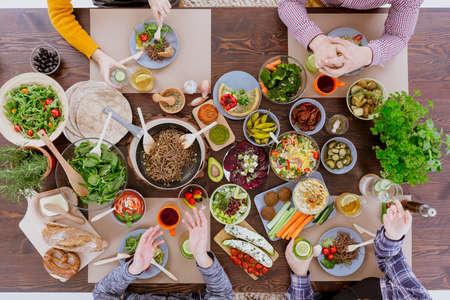 Různé veganské a vegetariánské jídlo ležící na rustikálním stole