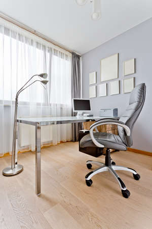 swivel chair: Modern grey office with a big desk, computer, diplomas hanging on the wall and a swivel chair Stock Photo