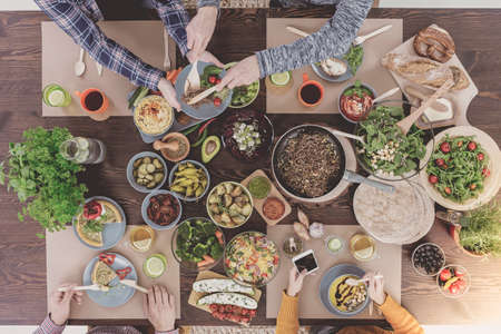 four people: Four people having dinner, sitting at wood table Stock Photo