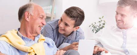 three generations: Three generations of men having fun together looking at photos Stock Photo