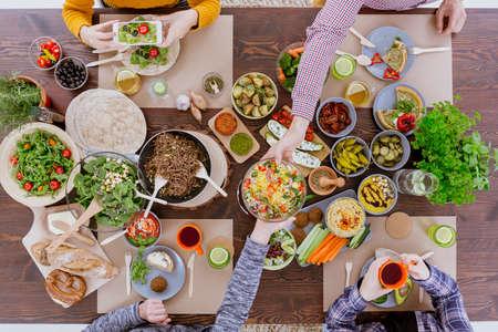 소박한 테이블에 앉아 채식 잔치를 가진 친구 스톡 콘텐츠